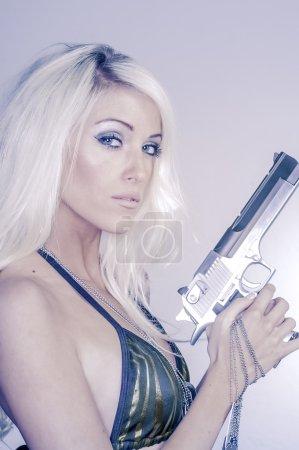Beautiful blond young woman holding gun