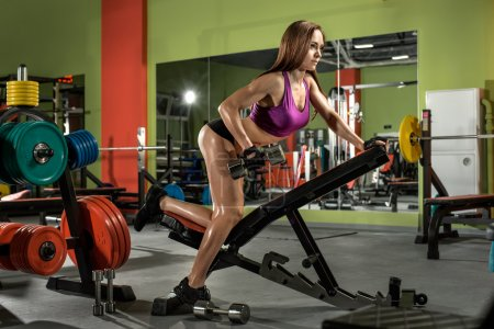 fitness girl  execute exercise with  dumbbells