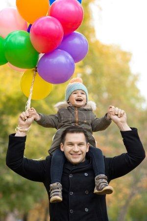 Photo pour Père heureux vomir petit enfant avec des ballons à air, sortie dans le parc d'automne - image libre de droit