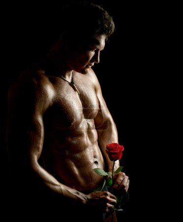 Photo for The very muscular handsome sexy guy with rose on black background, naked  torso - Royalty Free Image