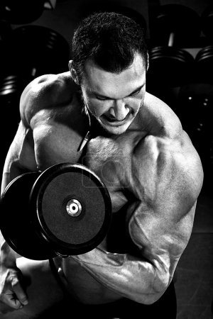 Photo for Vertical close up portrait handsome guy bodybuilder ,  execute exercise with  dumbbells, in dark gym, balck and white photo - Royalty Free Image