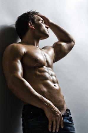 Photo pour Le très musclé beau mec sexy sur fond de mur gris - image libre de droit
