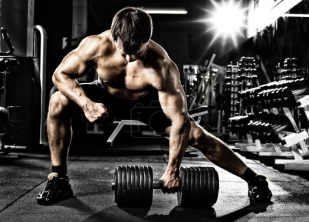 Photo for Very power athletic guy ,  execute  traction with  dumbbells, exercise on broadest muscle of back, in sport hall - Royalty Free Image