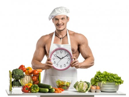 Photo for Man bodybuilder in white toque blanche and cook protective apron, hold on hands clock , on whie background, isolated - Royalty Free Image