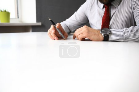 male hand pointing at business document during discussion at meeting