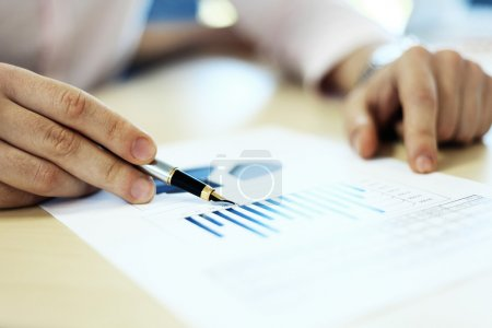 Business adviser analyzing financial figures denoting the progress in the work of company