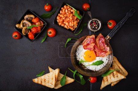 Photo pour Petit déjeuner anglais œufs frits, haricots, tomates, champignons, bacon et pain grillé. Vue du dessus - image libre de droit