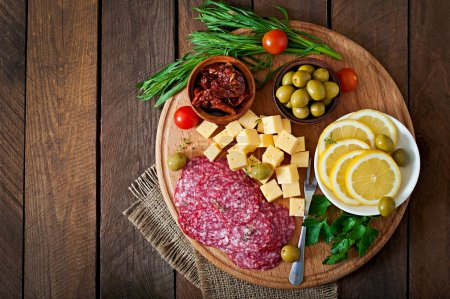 Photo for Antipasto catering platter with salami and cheese on a wooden background - Royalty Free Image