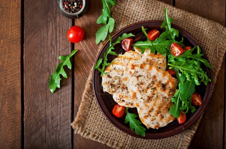 Photo for Chicken breast with fresh salad - arugula and tomatoes - Royalty Free Image