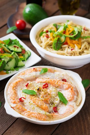 Baked slices of red and white fish with honey and lime juice, served with fresh salad and soft noodles