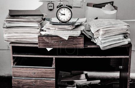 Photo for Messy workplace with stack of old paper and alarm clock - Royalty Free Image