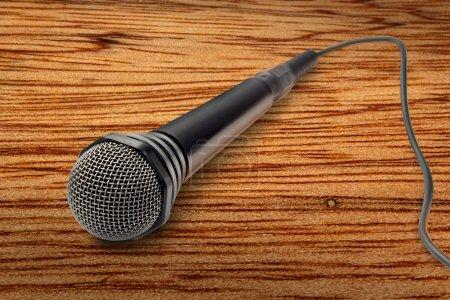 Photo pour Microphone noir sur fond en bois en gros plan - image libre de droit