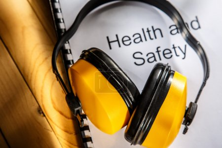 Photo for Health and safety register with earphones on wood - Royalty Free Image