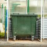 Photo of single green garbage bin outside...