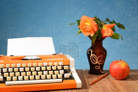 Typewriter apples and flowers in a vase