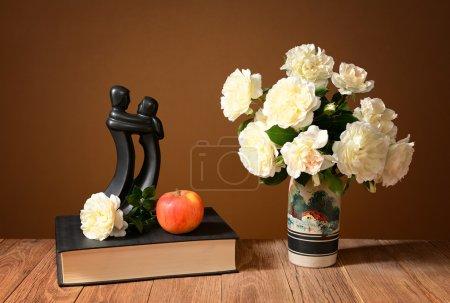 Strauß weißer Rosen in einer Keramikvase, Bücher und Apfel