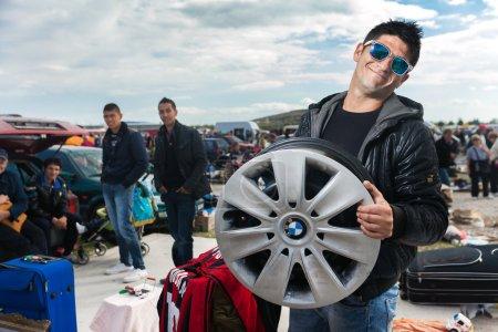 salesman holding used car rim