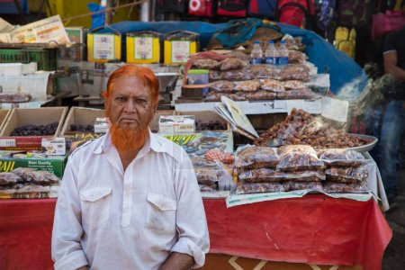 Indian vendor  sits next to street stall