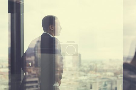 Photo for Business man looking out through the office balcony seen through glass doors. Post processed with vintage filter - Royalty Free Image