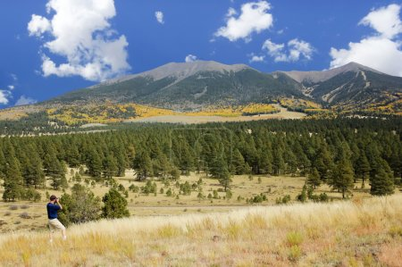 A Man Photographs the San Francisco Peaks in Fall