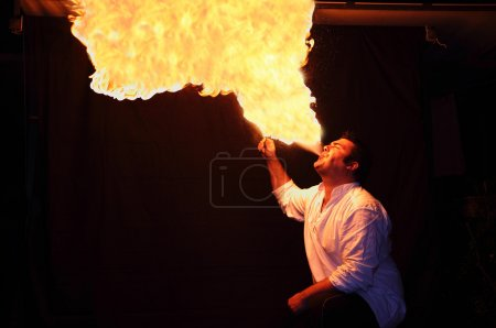 Fire-eater with flame over dark background...