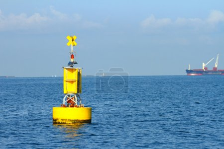Floating yellow navigational buoy on blue sea, gul...