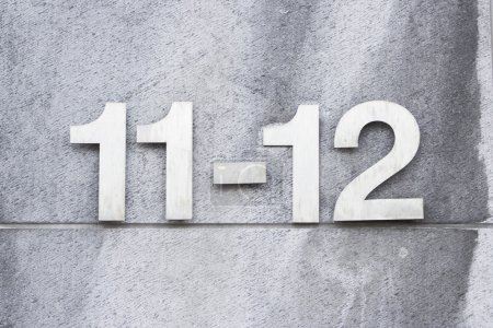 Photo for Number 12-11 on a wall, detail of house numbers on figures - Royalty Free Image
