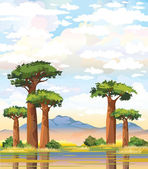 Baobabs and mountain on a cloudy sky.