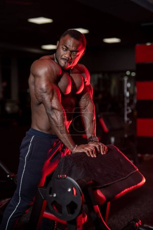 Photo for Sportsman shows muscular body and poses on gym background. African american fitness trainer. Closeup. - Royalty Free Image