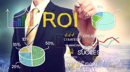 Photo pour Homme d'affaires dessin ROI (retour sur investissement) avec graphiques - image libre de droit