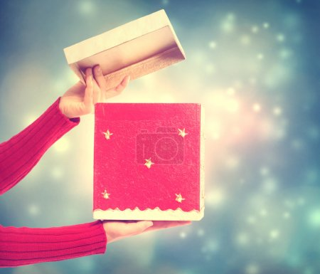 Photo for Woman holding a red gift box on holiday lights background - Royalty Free Image
