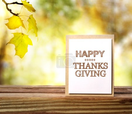 Photo for Happy Thanksgiving message card over fall leaves background - Royalty Free Image