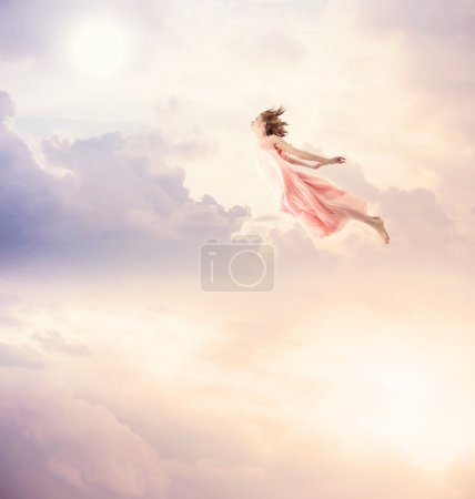 Girl in a pink dress flying in the sky. Serenity....
