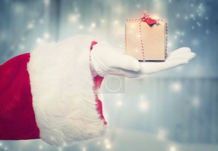 Photo for Santa Claus holding a small Christmas present box in snowy night - Royalty Free Image