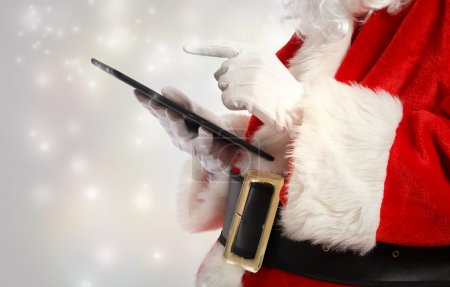 Photo for Santa Claus using a tablet in snowy night - Royalty Free Image