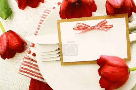 Photo for Romantic dinner table setting with blank note card and red tulips - Royalty Free Image