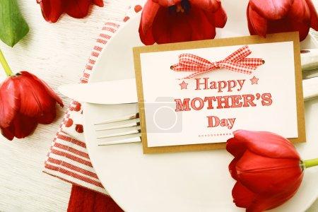 Photo pour Réglage de table de dîner avec carte de message de la fête des mères et tulipes rouges - image libre de droit