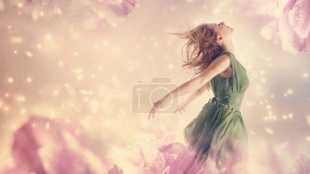 Photo pour Belle femme dans une robe verte dans un fantasme de fleur de pivoine rose - image libre de droit