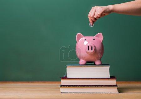 Photo pour Personne déposant de l'argent dans une tirelire rose sur des livres avec tableau en arrière-plan comme image conceptuelle des coûts de l'éducation - image libre de droit