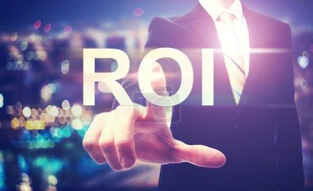 Photo pour Homme d'affaires pointant vers ROI (retour sur investissement) sur fond de ville floue - image libre de droit