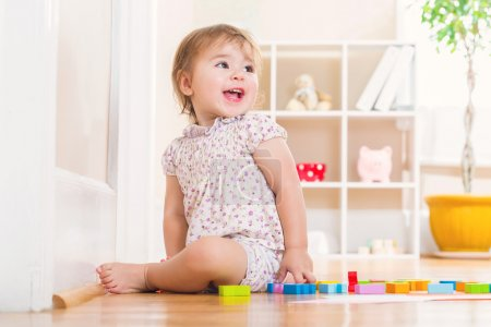Photo for Happy toddler girl with a big smile playing with wooden toy blocks inside her house - Royalty Free Image