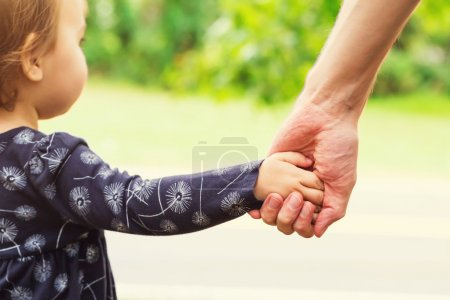 Toddler girl holding hands with her father