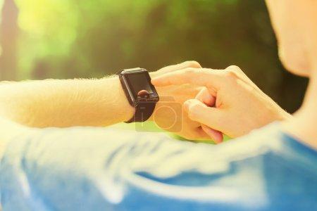 Photo pour Homme regardant sa montre intelligente dehors au coucher du soleil - image libre de droit