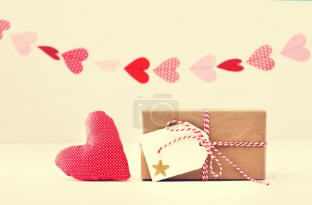 A garland of hearts above a small gift-wrapped box and textile heart