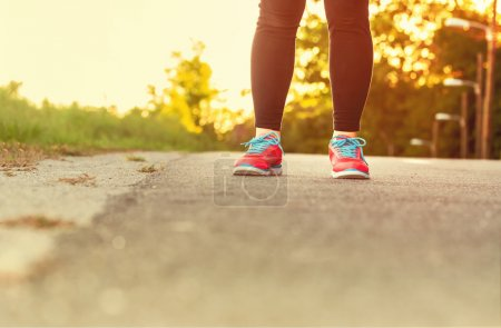 Female athlete in running shoes ready for a run on a forest path