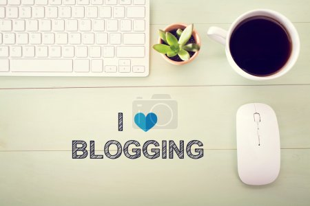 Photo for I Love Blogging concept with workstation on a light green wooden desk - Royalty Free Image