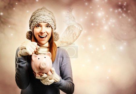 Happy woman depositing money into her piggy bank
