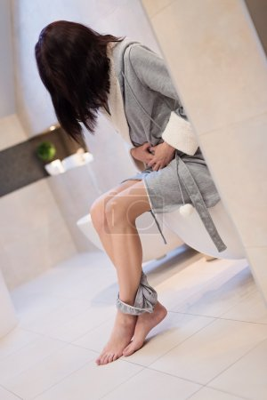 Brunette woman sitting on toilet in the bathroom.