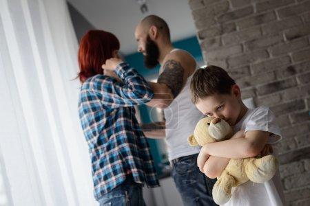 Photo pour Petit garçon triste et désespéré pendant la querelle des parents étreignant son ami vieil ours en peluche - image libre de droit