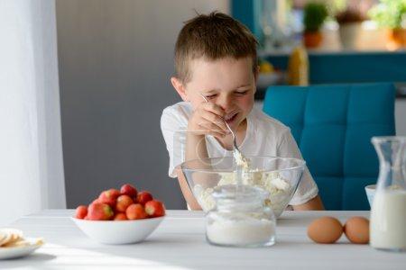Photo pour Garçon de 7 ans mélangeant du fromage blanc cottage dans un bol. Prépare des mini gâteaux au fromage avec des fraises - image libre de droit